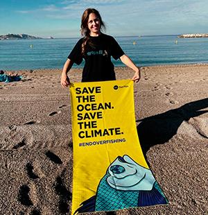 Mika, die Repräsentantin von WeMove, hält ein Handtuch mit der Aufschrift ,,Rettet den Ozean. Rettet das Klima.