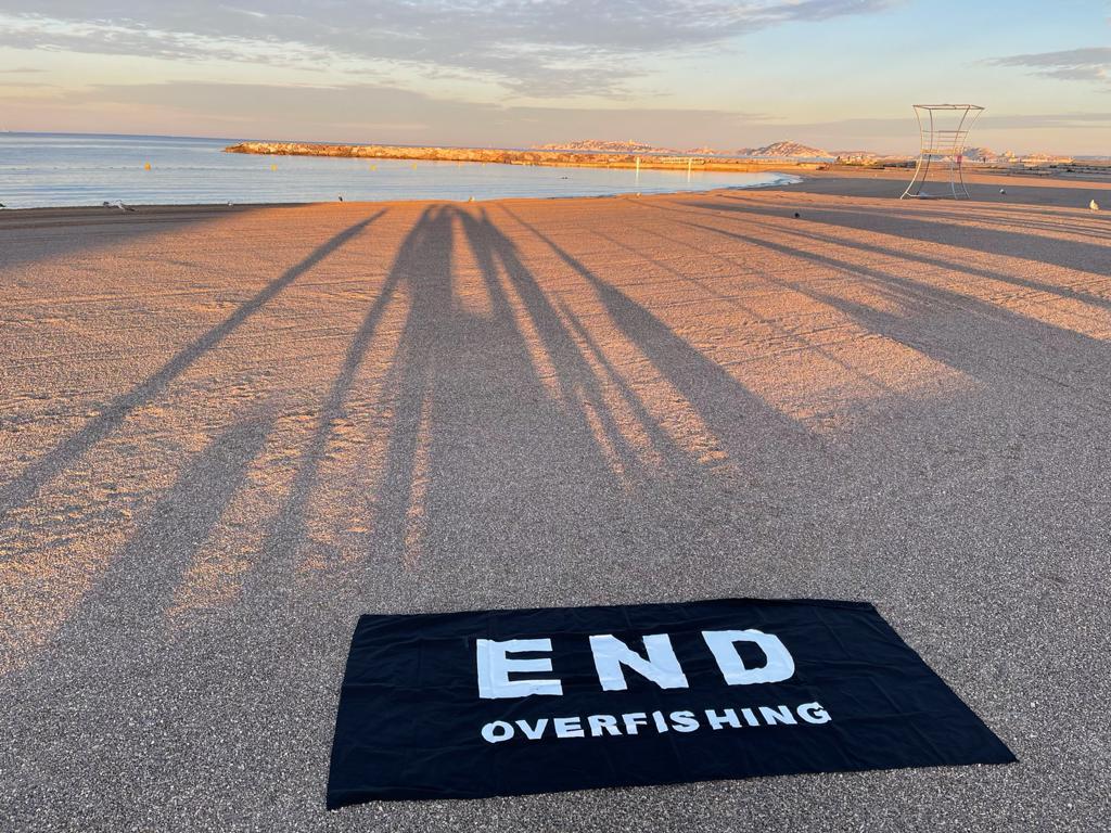 """Ein Handtuch mit der Schrift ,,Stoppt die Überfischung"""" am Strand von Marseille."""