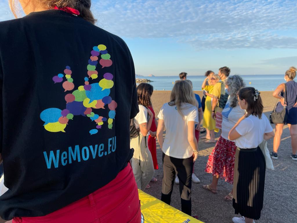 Die Teilnehmer bereiten sich auf das Schwimmen vor. Im Vordergrund trägt jemand ein T-shirt von WeMove Europe