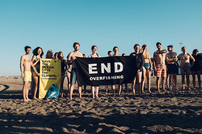 Die Teilnehmer stehen versammelt und halten ein Handtuch mit der Aufschrift 'Stoppt die Überfischung'