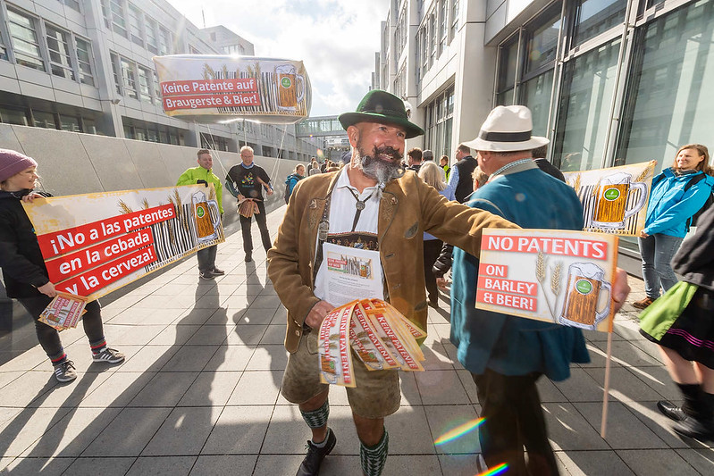 Man in traditional German clothes hands out No Patents flyers