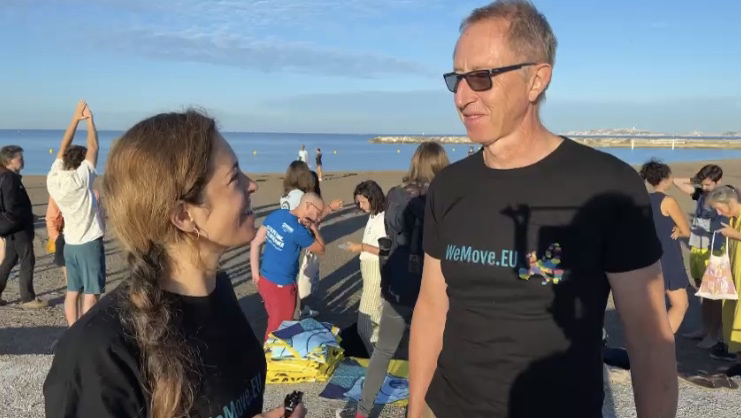 Mika, eine Koordinatorin von WeMove Europe, steht am Strand und spricht mit dem Segler Laurent über seine Erfahrungen.