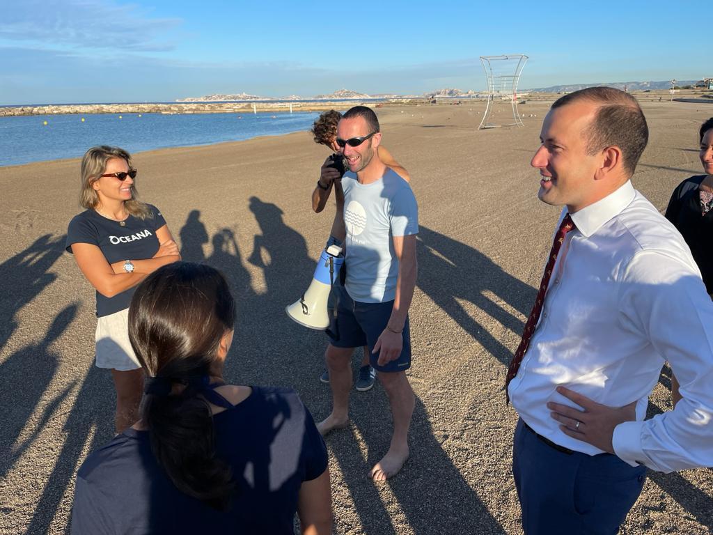 Der Kommissar Virginijus Sinkevičius steht im Anzug auf dem Strand und redet mit unseren Partnern von Oceana und Our Fish