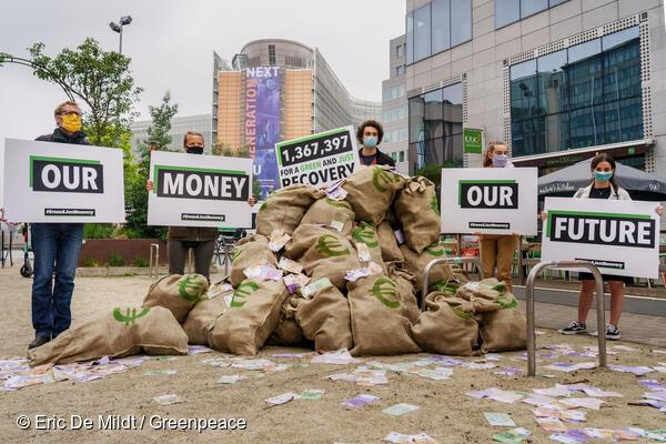 Eine Gruppe von Aktivistinnen und Aktivisten stehen um einen Haufen Geldsäcke. Scheine wirbeln im Wind. Die Schilder sagen: Our Money Our Future - Unser Geld unsere Zukunft. Die Anzahl der Unterschriften ist mit 1,3 Millionen angegeben. Sie sind in Brüssel.