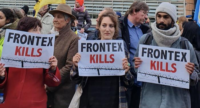 Drei Demonstrant/innen in Brüssel stehen vor dem Gebäude der EU-Kommission und halten Transparente mit der Aufschrift Frontex tötet.