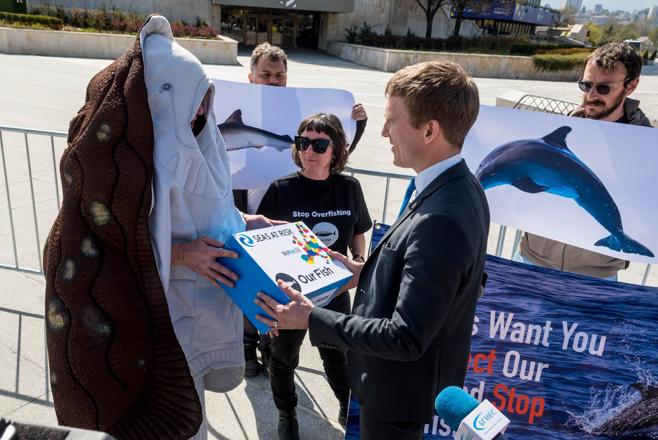 Ein Campaigner verkleidet als Rochen übergibt an einen Delegierten einen Karton gefüllt mit Unterschriften