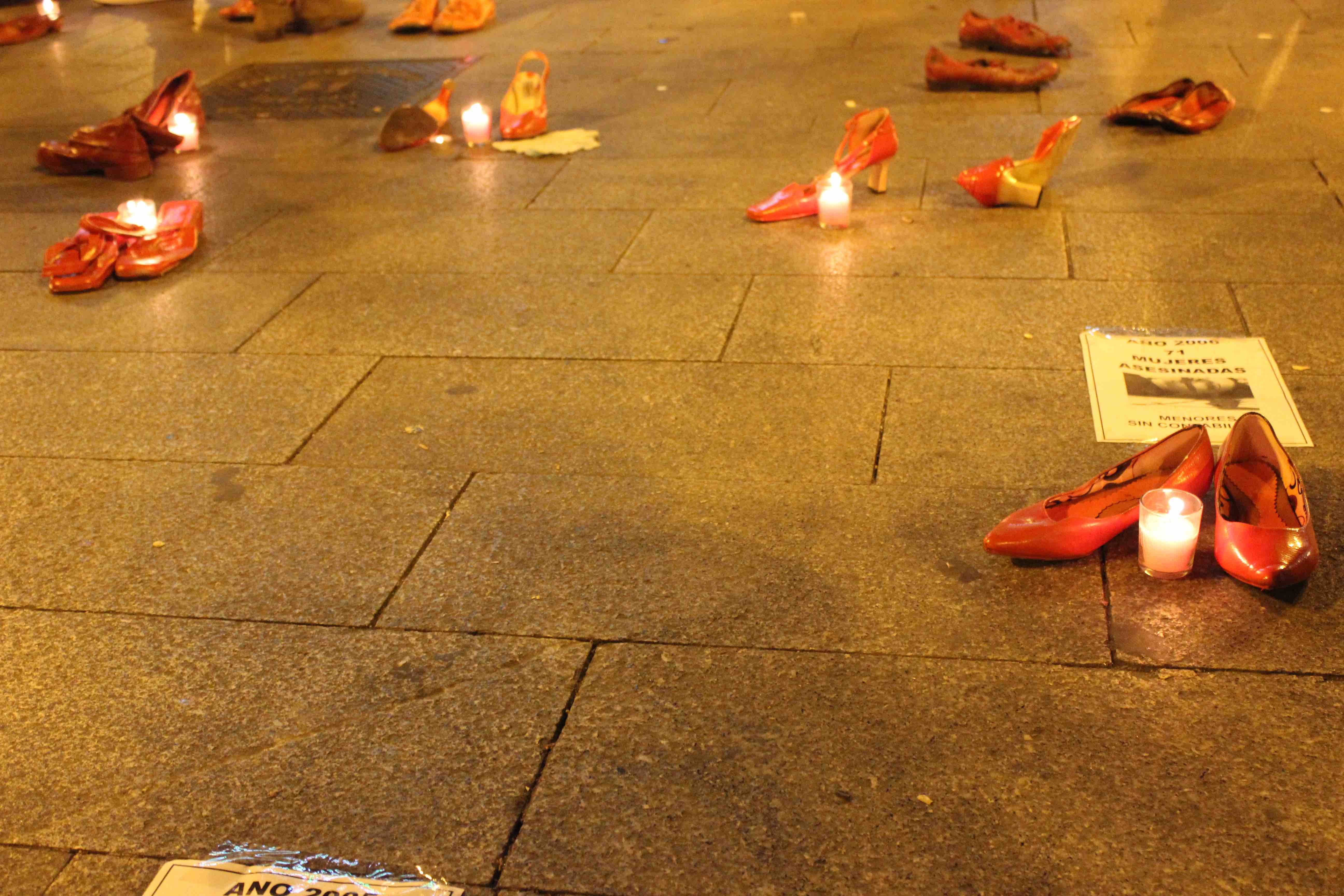 Shoes and candles laid out in memory of women killed in Europe