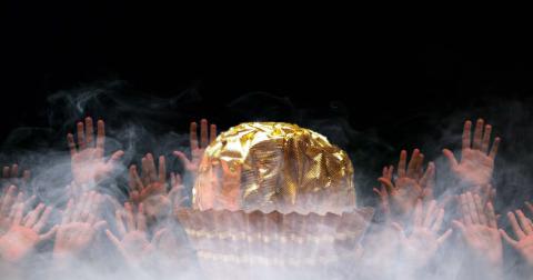 Imagen de un Ferrero Rocher rodeado de manos.