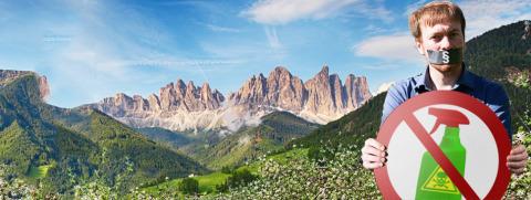 Cordillera y valle, a la derecha: hombre con pegatina sobre la boca con cartel no pesticidas